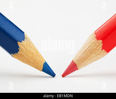 red and blue pencils against each other on a white paper sheet - Stock Photo