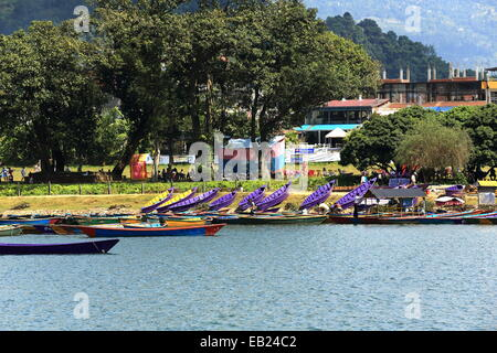 POKHARA, NEPAL - OCTOBER 12: Colorist wooden rowboats wait for the tourists and the locals going for a ride on lake - Stock Photo