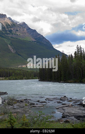 Fast running melt water beneath towering mountains in the Canadian Rocky Mountains. - Stock Photo