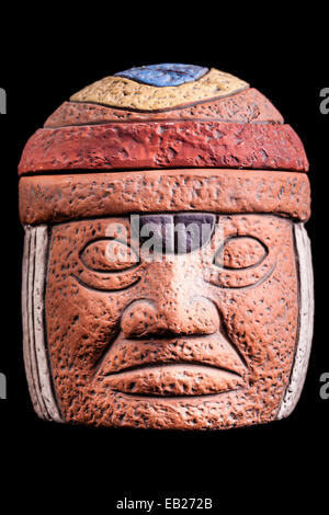 a terracotta olmec face idol souvenir isolated over a black background - Stock Photo