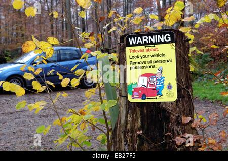 Warning sign about thieves in countryside car park - Stock Photo