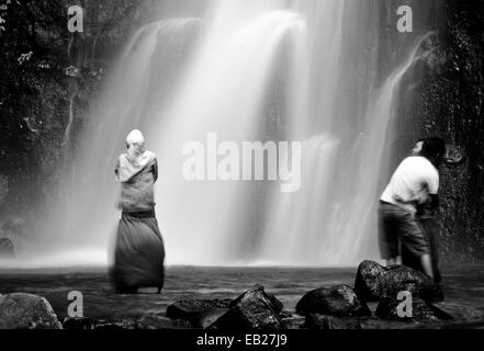 Couple embraces in this black and white high contrast image of love in a mist at a surreal tropical waterfall created - Stock Photo
