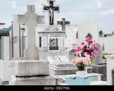 Marble and stone Christian graves with crosses and grave offering of bright pink flowers in the Panteon de San Roman - Stock Photo