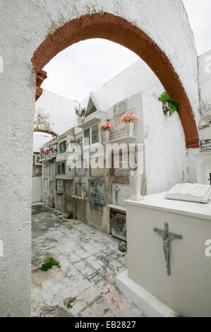 Stacked white graves seen through an orange archway in background with an altar tomb in foreground Panteon_de_San - Stock Photo