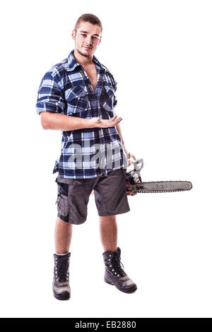 a young lumberjack wearing a checkered shirt holding a chainsaw and showing something isolated over white background - Stock Photo