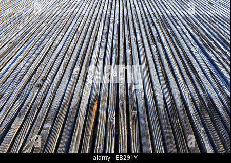 Frost begins melting on a  walkway made from wooden slats - Stock Photo