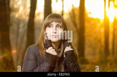 Portrait of young beautiful girl in evening autumn forest - Stock Photo