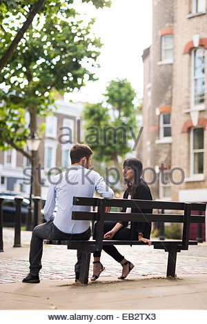 A couple sitting on a park bench in Primrose Hill in London - Stock Photo