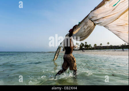 A fisherman carries the tarpaulin sail and mast from his wooden trimaran sailing dhow to shore at sunset. - Stock Photo