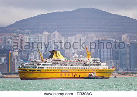 A yellow cruise ship anchored in Victoria Harbor, in front of Hong Kong's skyline. - Stock Photo