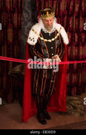 Royal king cutting a red ribbon with scissors - Stock Photo