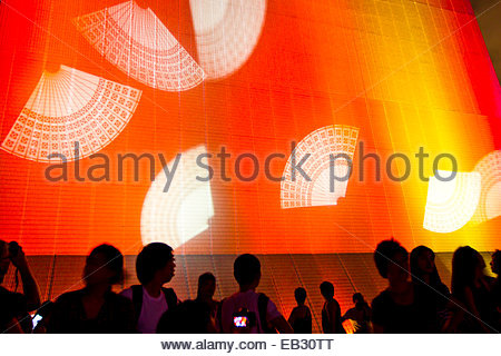 Red and yellow lights illuminate a building as people watch the Symphony of Lights laser and light show over the - Stock Photo