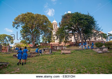 School girls wearing uniforms walk in a cemetery by Saint Johns Cathedral at recess. - Stock Photo