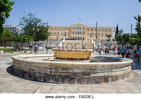 A fountain in Syntagma Square with the Greek Parliament building in the background in Athens, Greece - Stock Photo