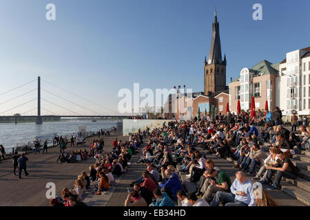 People sitting on a flight of steps in the evening sun, Burgplatz square with St Lambertus church, historic center, - Stock Photo