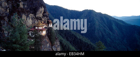 An ancient Buddhist monastery perched on a sheer cliff face above a forested valley in the Himalaya. - Stock Photo