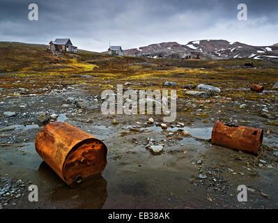 Old rusty barrels, abandoned houses at back, Krossfjorden, Haakon VII Land, Spitsbergen Island, Svalbard Archipelago - Stock Photo