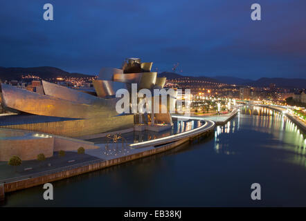 A view of the Guggenheim Museum Bilbao and the Nervion River at night. - Stock Photo