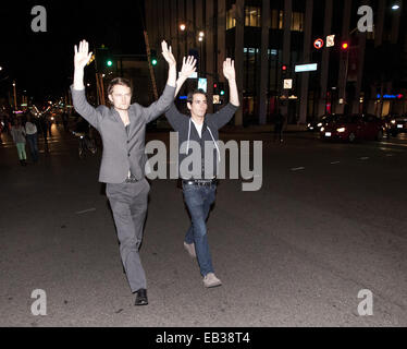 Los Angeles, California, USA. 24th Nov, 2014. Two young men with hands raised over their heads walk west along Wilshire - Stock Photo