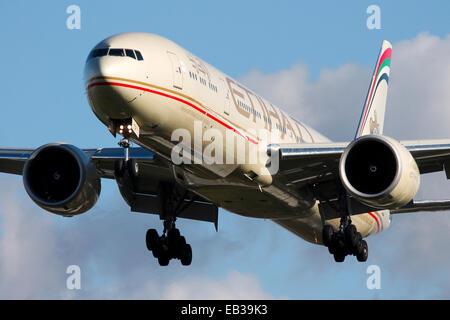 Etihad Airways Boeing 777-300 approaches runway 27L at London Heathrow airport. - Stock Photo