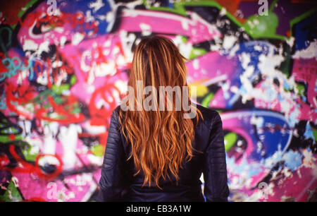 France, Rear view of young woman in front of colorful mural - Stock Photo