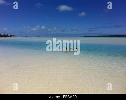 Mother and three children swimming in sea, Cook Islands - Stock Photo