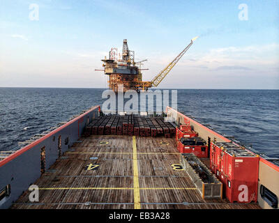 Nautical vessel approaching an oil platform at sunrise