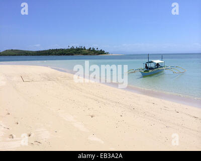 Philippines, Bicol Region, Camarines Sur, Caramoan, Bangka idling in shallow waters, tied to pole stuck into beach - Stock Photo