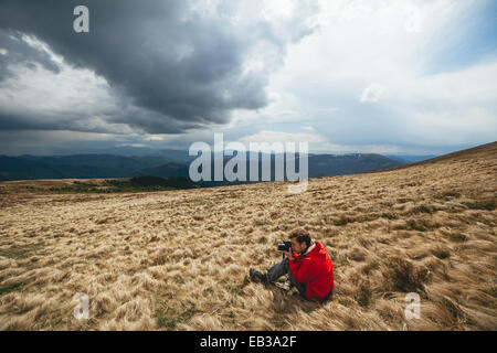 Young man wearing red sweater sitting withered grass photographing - Stock Photo