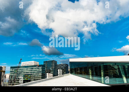 Norway, Oslo, National Oslo Opera House, Partial view of roof with highrise buildings in background - Stock Photo