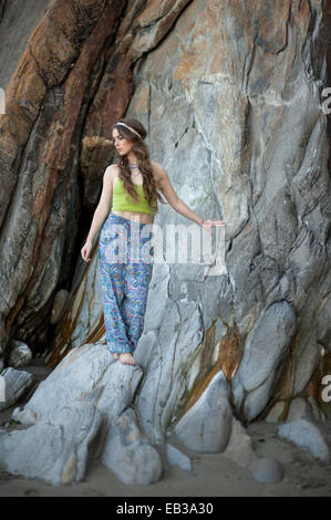 Young woman standing on rocks on beach - Stock Photo