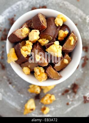 Chocolate candy bars cut into pieces mixed with honeycomb in white porcelain bowl - Stock Photo