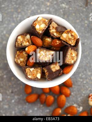 Chocolate candy bars cut into pieces mixed with whole almonds in white porcelain bowl - Stock Photo
