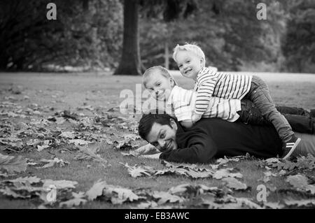 Portrait of father and sons lying on grass - Stock Photo
