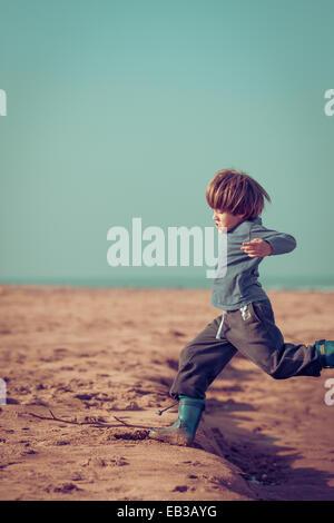 Boy running on beach, Morocco - Stock Photo