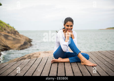 Woman sitting on wooden deck overlooking lake - Stock Photo