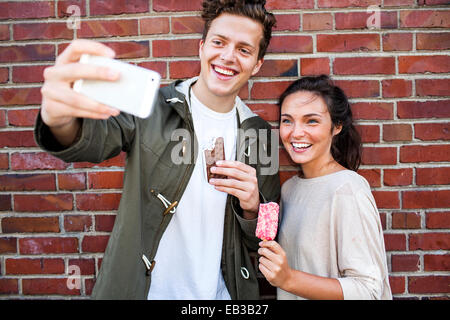 Caucasian couple taking selfie near red brick wall - Stock Photo