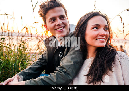 Caucasian couple sitting together on beach - Stock Photo