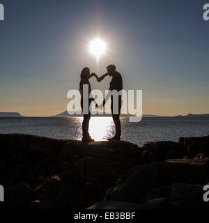 Man and Woman making heart silhouette - Stock Photo