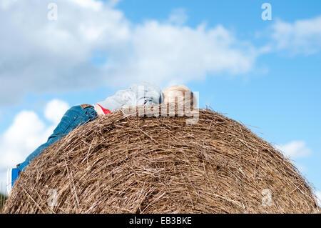 Boy lying on hay bale - Stock Photo