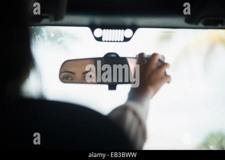 Caucasian woman adjusting rear view mirror in car - Stock Photo