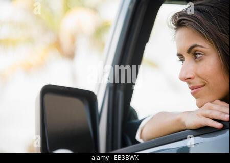 Caucasian woman leaning on car window - Stock Photo