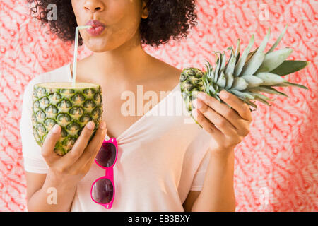 Woman drinking juice from fresh pineapple Stock Photo