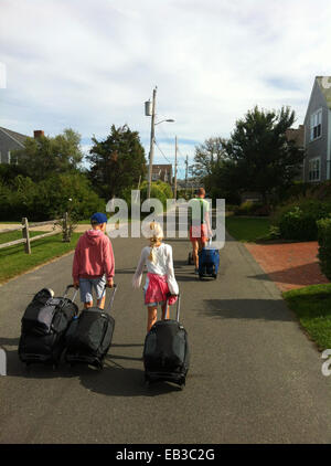 Father with two children walking down road pulling suitcases, Norway - Stock Photo