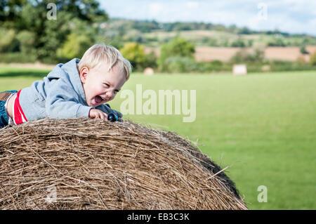 Boy crawling on hay bale laughing - Stock Photo
