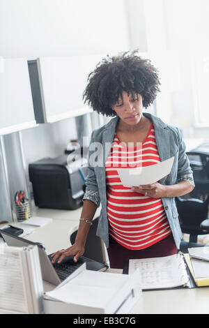 Pregnant African American businesswoman working in office - Stock Photo