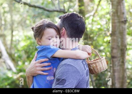 Girl standing in forest hugging her father - Stock Photo