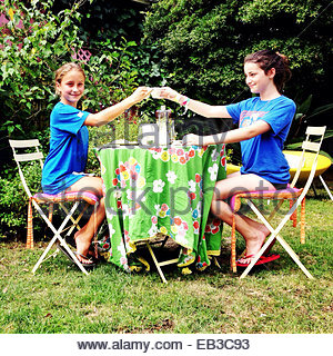 Two girls sitting in garden making a celebratory toast with cups of tea - Stock Photo