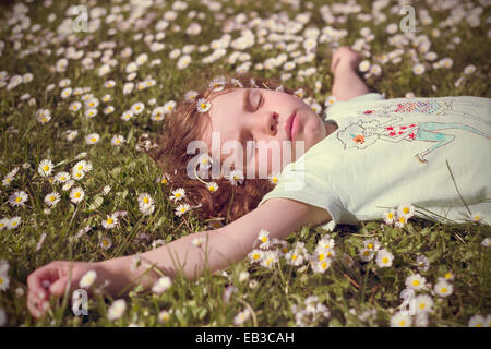 Girl lying in a field of daisy flowers - Stock Photo