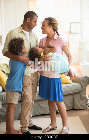 Family smiling together in living room - Stock Photo